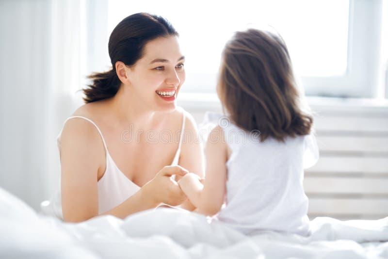 Het meisje en haar moeder genieten van zonnige ochtend royalty-vrije stock afbeeldingen