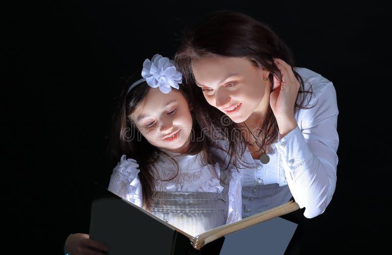 Het meisje en haar moeder lezen een interessant sprookje Geïsoleerde op zwarte achtergrond royalty-vrije stock foto