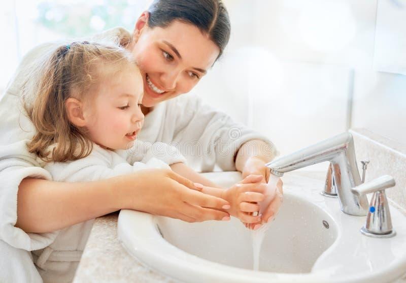 Het meisje en haar moeder wassen handen royalty-vrije stock afbeelding