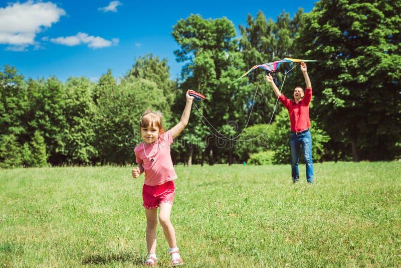 Het meisje en haar vader spelen met een vlieger stock foto
