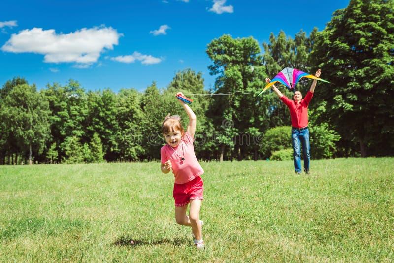 Het meisje en haar vader spelen met een vlieger stock foto's