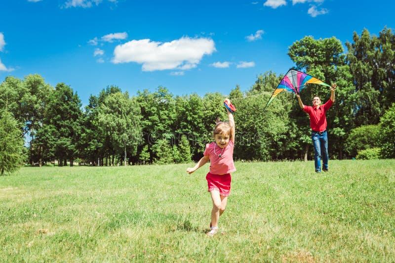 Het meisje en haar vader spelen met een vlieger royalty-vrije stock foto