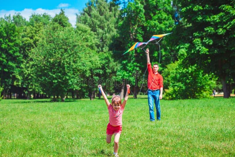 Het meisje en haar vader spelen met een vlieger stock fotografie