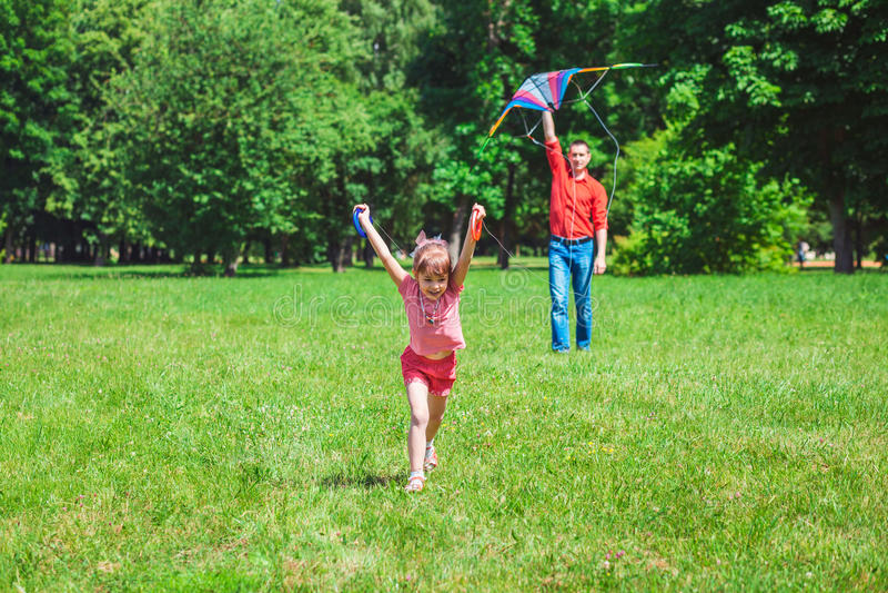 Het meisje en haar vader spelen met een vlieger royalty-vrije stock afbeeldingen