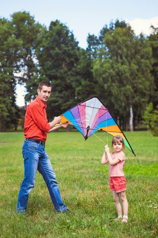 Het meisje en haar vader spelen met een vlieger royalty-vrije stock fotografie