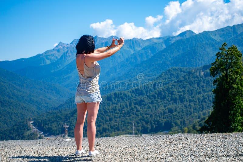 Het meisje fotografeert het berglandschap op smartphone stock afbeelding