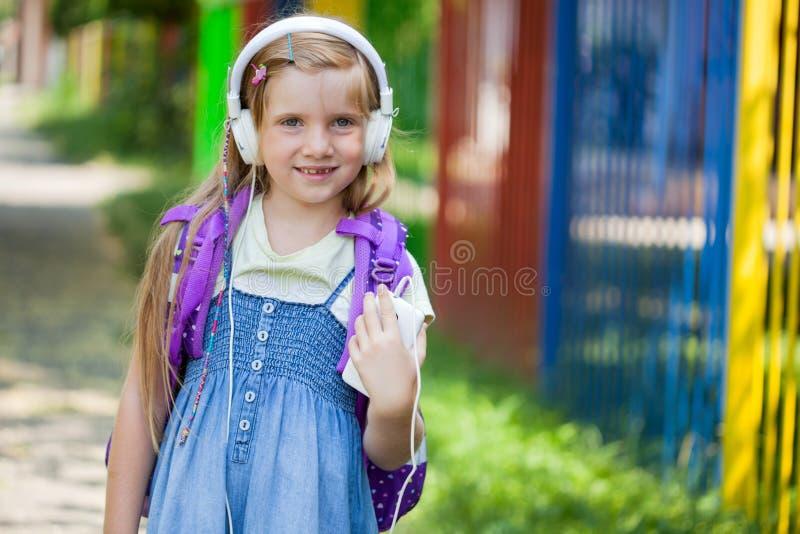 Het meisje gaat naar school en luistert aan muziek via smartphone stock foto