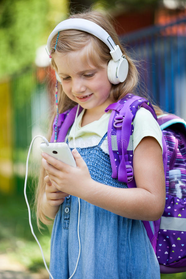 Het meisje gaat naar school en luistert aan muziek via smartphone stock foto's