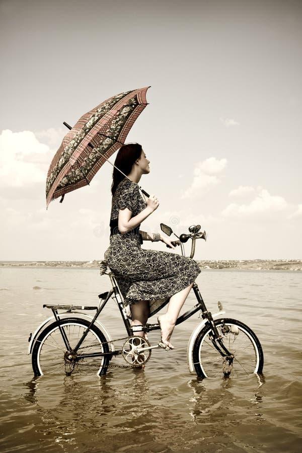 Het meisje gaat voor een cyclusrit bij water met paraplu royalty-vrije stock fotografie