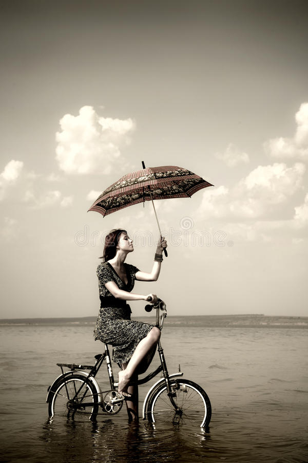 Het meisje gaat voor een cyclusrit bij water met paraplu stock foto