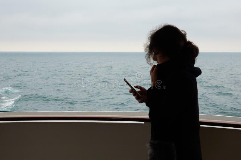 Het meisje gebruikt cellulaire mededeling en Internet op een smartphone in het overzees op een cruisevoering stock foto's