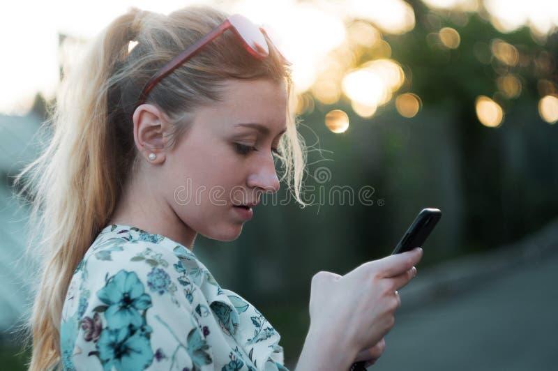 Het meisje gebruikt de telefoon bij zonsondergang in het park stock afbeeldingen