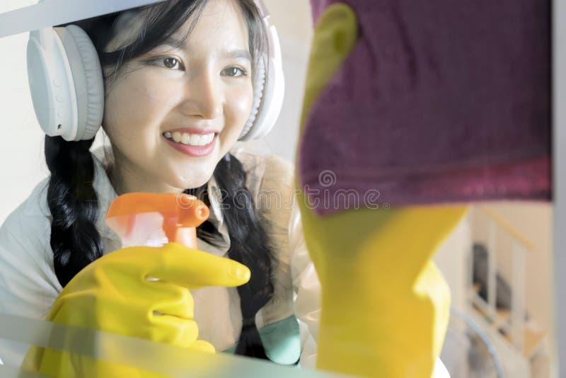 Het meisje gebruikt een handdoek om het glazen venster af te vegen stock foto