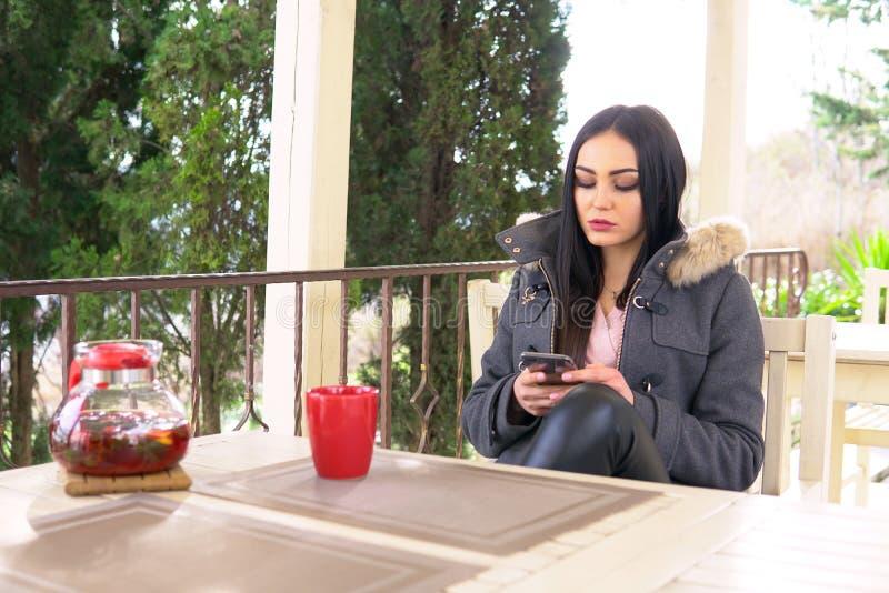 Het meisje gebruikt een smartphonelunch in het restaurant royalty-vrije stock afbeelding