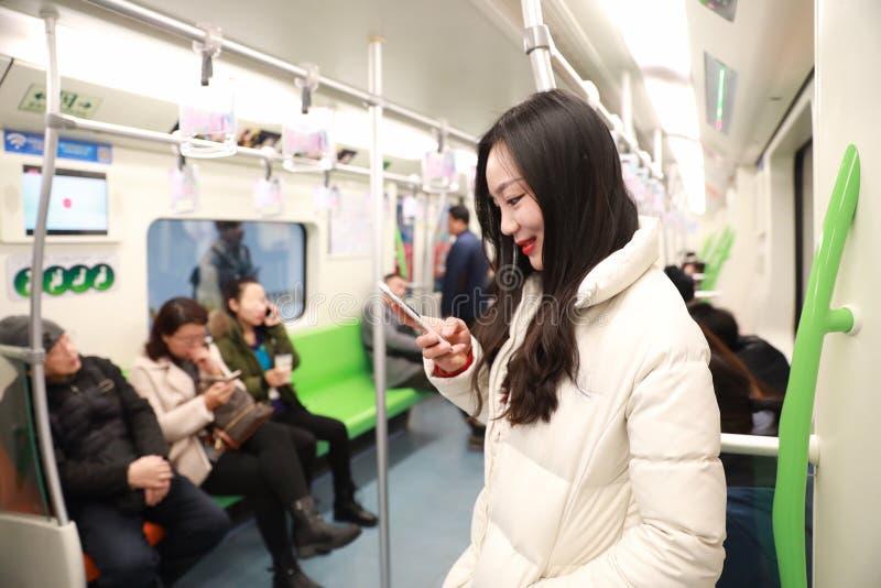 Het meisje gebruikt mobiele telefoon terwijl reis door metro, Vrouw gebruikend haar celtelefoon in Metro stock fotografie