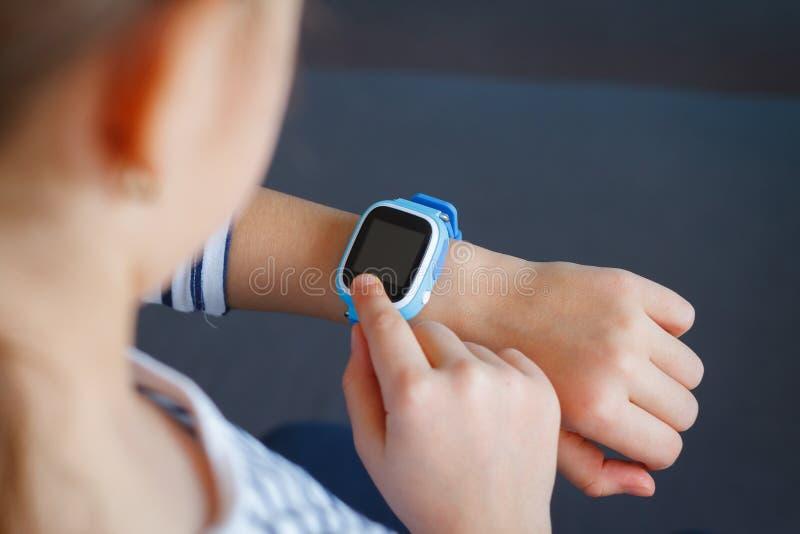 Het meisje gebruikt smartwatch telefoon stock fotografie