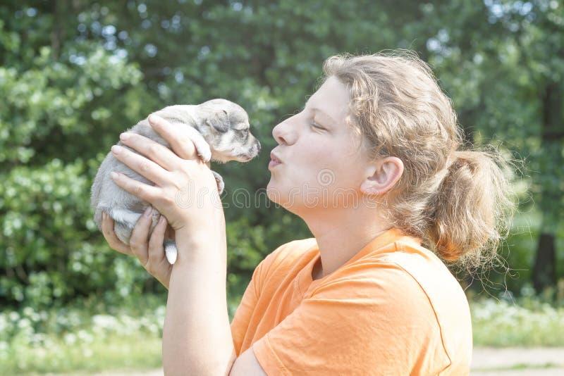 het meisje geeft bijna een kus aan het puppy Op handen er zijn het stemmen royalty-vrije stock afbeelding