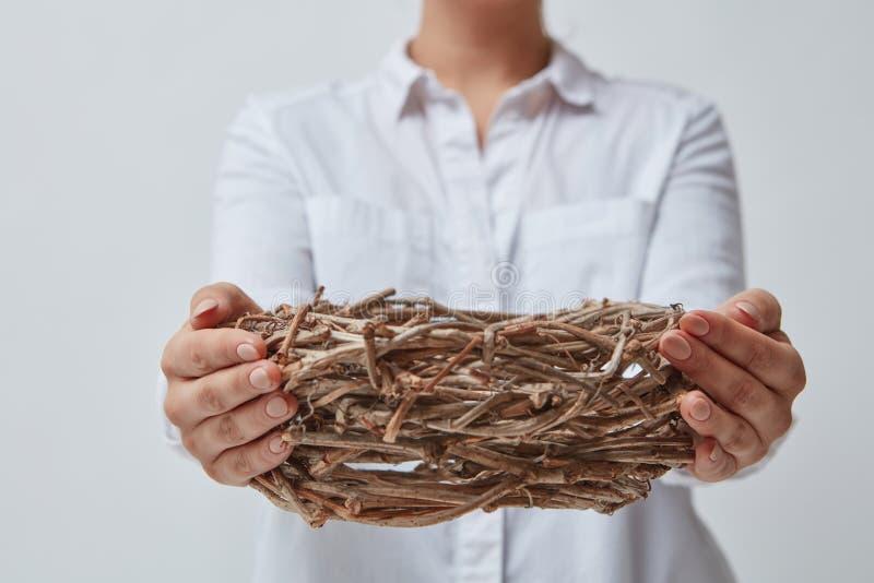 Het meisje geeft een leeg nest van takken stock afbeeldingen