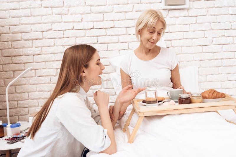 Het meisje geeft thuis voor bejaarde Het meisje brengt ontbijt op dienblad stock afbeelding