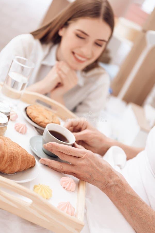 Het meisje geeft thuis voor bejaarde Het meisje brengt ontbijt op dienblad De vrouw drinkt koffie royalty-vrije stock foto