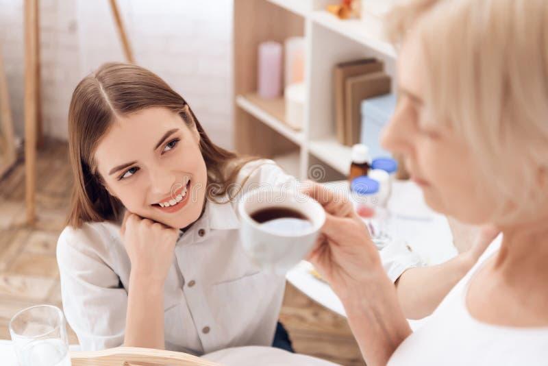 Het meisje geeft thuis voor bejaarde Het meisje brengt ontbijt op dienblad De vrouw drinkt koffie stock fotografie