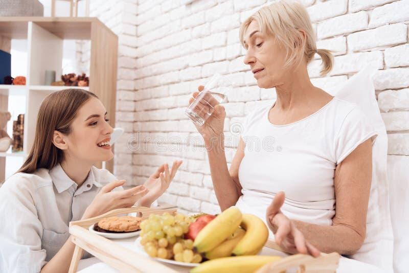 Het meisje geeft thuis voor bejaarde Het meisje brengt ontbijt op dienblad De vrouw is drinkwater royalty-vrije stock afbeelding
