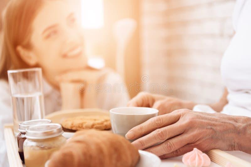 Het meisje geeft thuis voor bejaarde Het meisje brengt ontbijt op dienblad Het meisje glimlacht royalty-vrije stock foto's