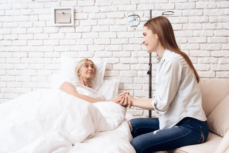 Het meisje geeft thuis voor bejaarde Zij houden handen royalty-vrije stock foto's