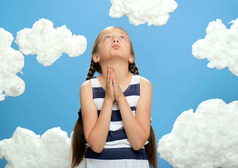 Het meisje gekleed in het gestreepte kleding stellen op een blauwe achtergrond met katoenen wolken, het kijken omhooggaand en het stock foto's