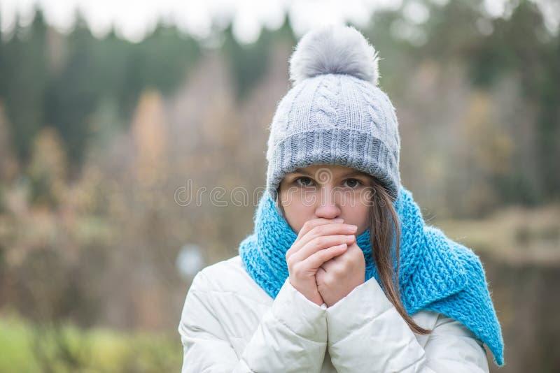 Het meisje is gekleed in warme kleren, warme handen De herfst, koude buitenkant royalty-vrije stock afbeeldingen