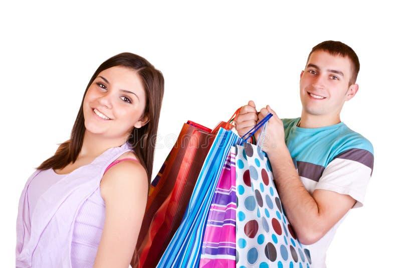 Het meisje is gelukkig terwijl mens dragen die in zakken doet winkelt royalty-vrije stock fotografie