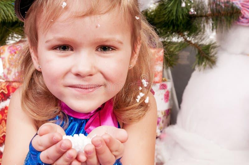 Het meisje geniet van de sneeuw en vangt het met zijn handen stock afbeelding