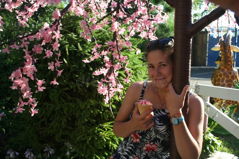 Het meisje geniet van de zon en de bloemen en eet roomijs royalty-vrije stock fotografie