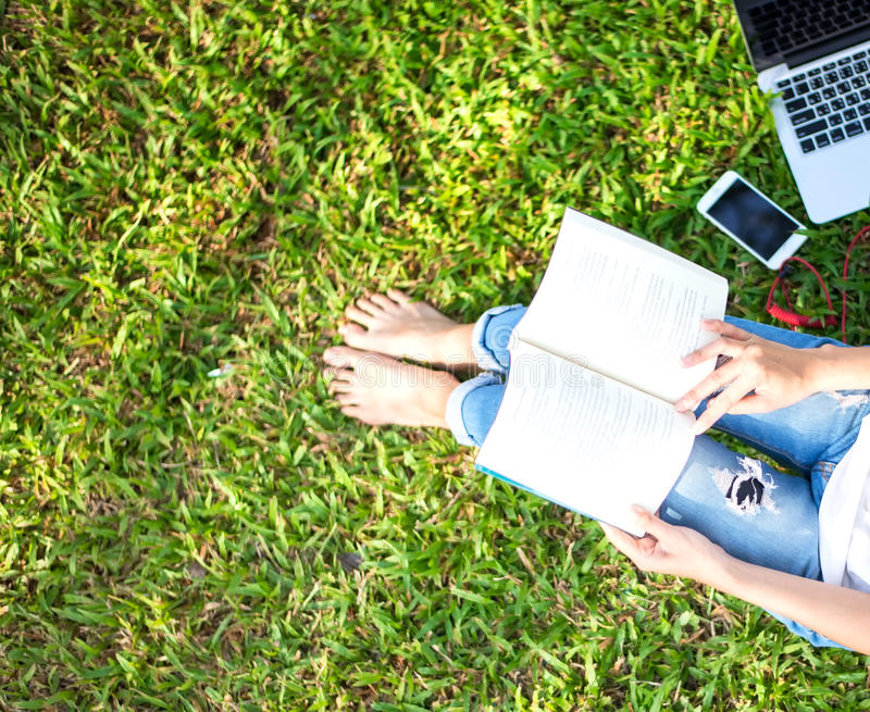 Het meisje geniet van lezend die boek en speelt laptop op het gras van park wordt ingediend stock fotografie