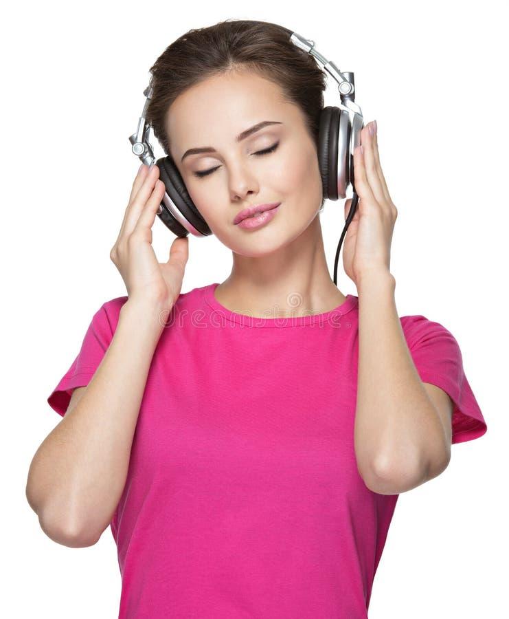 Het meisje geniet van luister aan muziek op hoofdtelefoons stock fotografie