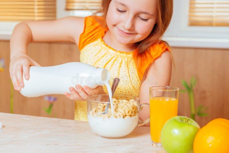 Het meisje giet melk voor gezond ontbijt royalty-vrije stock foto's