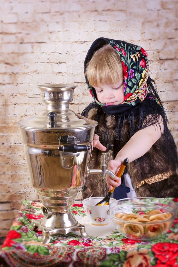 Het meisje giet thee van een samovar stock foto