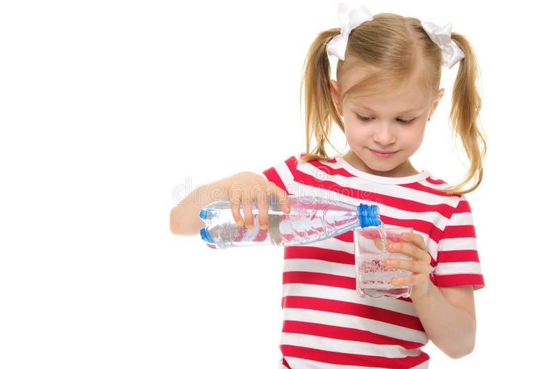 Het meisje giet water van fles in glas stock foto