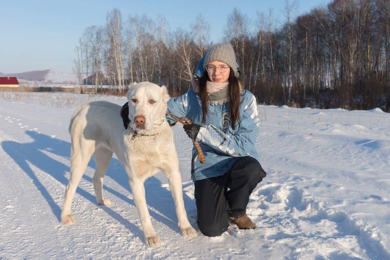 Het meisje ging zitten met een grote witte herdershond aan de kant van de weg amid het bos royalty-vrije stock afbeeldingen