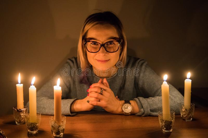 Het meisje in het glas zit dichtbij de lijst met kaarsen in een donkere ruimte royalty-vrije stock afbeeldingen