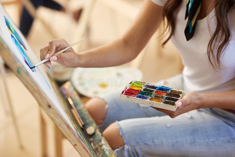 Het meisje in glazen gekleed in witte t-shirt en jeans met een sjaal rond haar hals schildert een beeld in de kunststudio stock foto's