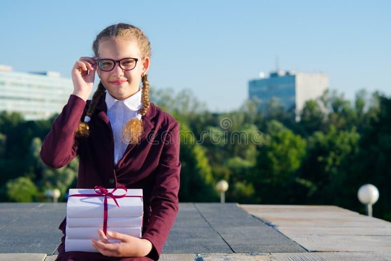 Het meisje in glazen houdt handboeken op haar overlapping, in openlucht zittend stock fotografie