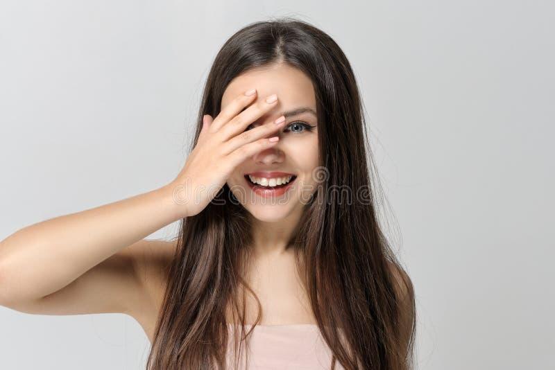 Het meisje glimlacht en behandelt haar ogen met haar hand stock afbeeldingen