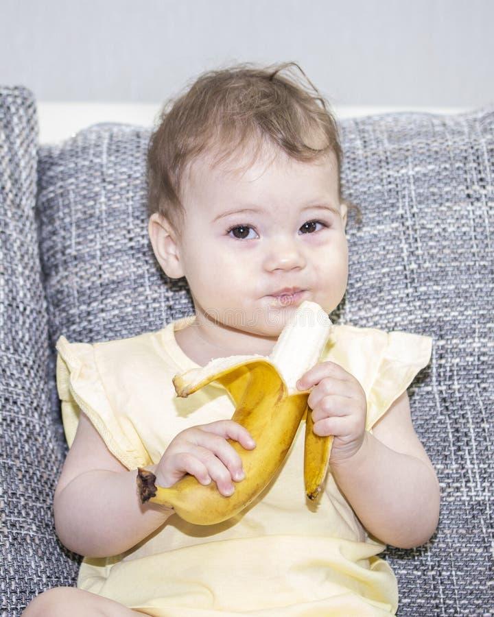 Het meisje glimlacht en houdt slyly een banaan in haar handen Het kind eet exotische vruchten Het babymeisje met een sluwe grijns royalty-vrije stock afbeelding