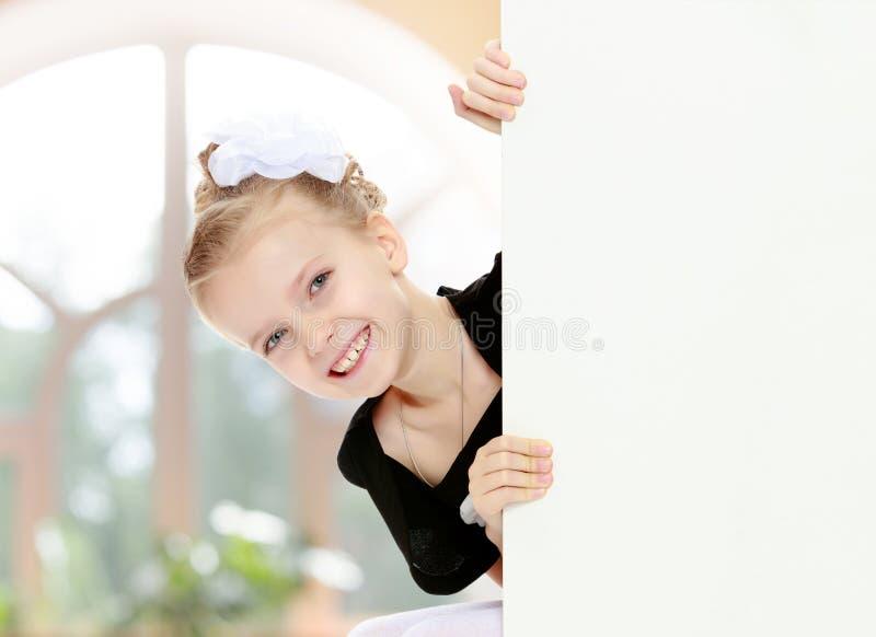Het meisje gluurt uit van achter witte banner stock fotografie