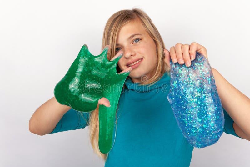 Het meisje groen houden en een blauw die schitteren slijm stock fotografie