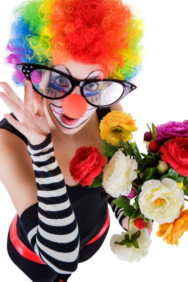 Het meisje in groot rood glazen en clownkostuum met een boeket van bloemen kijkt omhoog royalty-vrije stock afbeelding