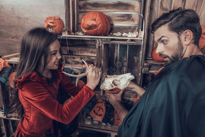 Het meisje in Halloween-Kostuum doet schrikken de Jonge Mens stock foto
