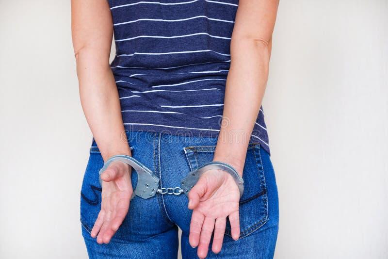 Het meisje in handcuffs bij het politiebureau Gearresteerd voor misdemeanors stock afbeeldingen