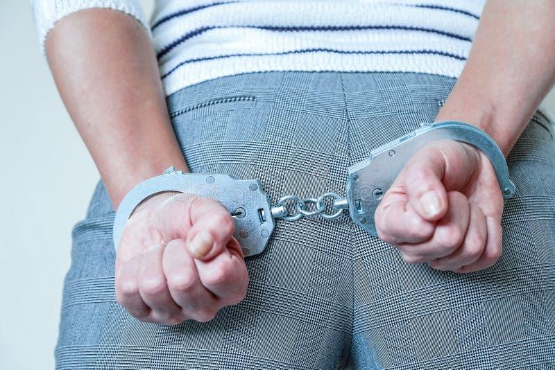 Het meisje in handcuffs bij het politiebureau Gearresteerd voor misdemeanors stock foto